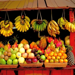 A photo of various tropical fruits at a market stand, including bananas, dragon fruit, pineapples, mangoes, and apples